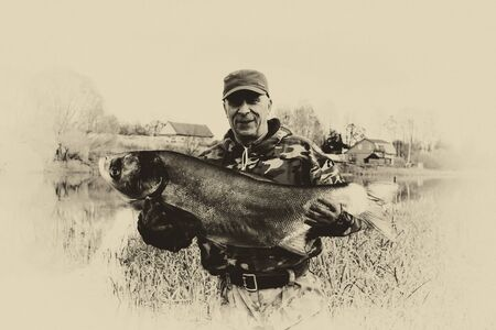 Happy and lucky fisherman holds a large fish that he caught. Vintage photo.