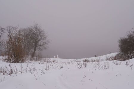 Winter landscape in the mist. The hill on top of which are two snowmen. There are a lot of snow. Banque d'images