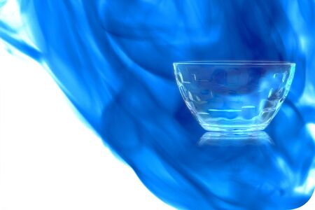 Empty glass dessert bowl on white background enveloped in puff of blue smoke.