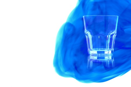 Empty glass for whiskey on white background enveloped in puff of blue smoke.