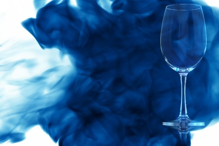 An empty glass of red wine or water on white background enveloped in puff of blue smoke. Banque d'images