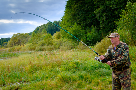 Fisherman with rod fishing on a beautiful lake Banque d'images