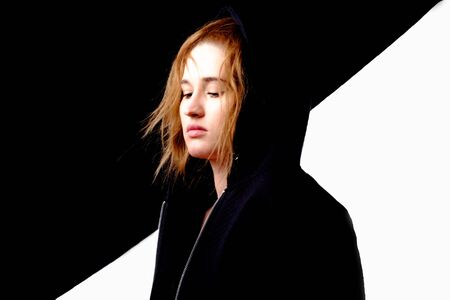 The girl looks down. Girl on a black and white photo looking down. On it black jacket and hood. Banque d'images
