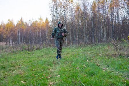The old man in the camouflage suit runs in the forest. In the foreground the meadow, back forest.