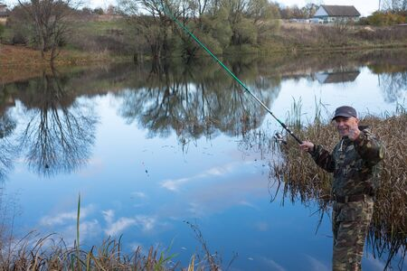 A man catches fish in the lake. Around autumn sparkle colors. The lake reflected the blue sky with white clouds and trees around the lake. Banque d'images