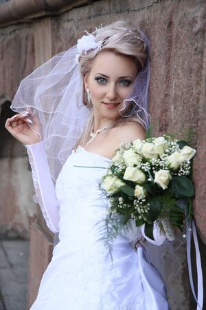 bride with  wedding bouquet Against  stone wall  photo