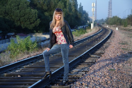 girl stands on  railway way Summer, evening  photo