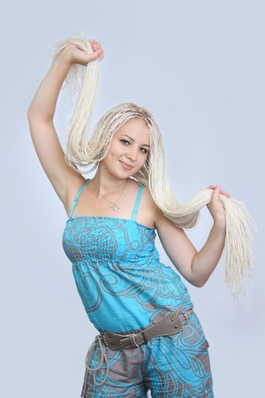 young girl with small plaits and piercing  On  grey background  photo
