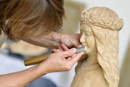 trinchante: tallador de madera con un cincel en el trabajo