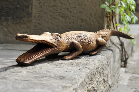 woodcutting: carved wooden crocodile on stone
