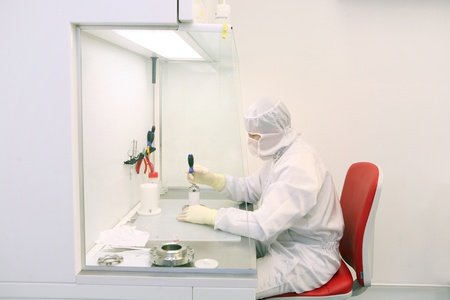 technician working in a clean room in a microscopes producing factory Stock Photo - 8994821