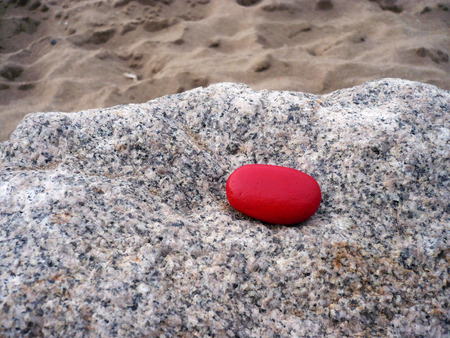 red pebble: red pebble on rock Stock Photo