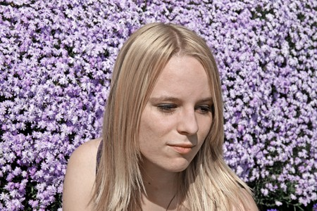 17 years: Blond girl (17 years) in front of a flowerbed from moss phlox in Germany, Europe