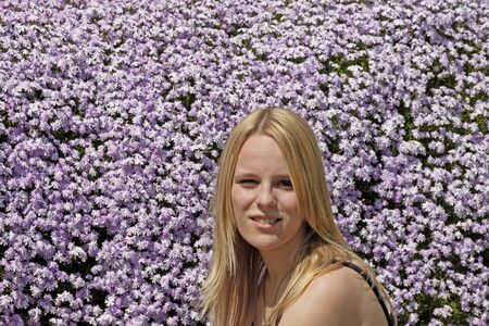 17 years: Blond girl (17 years) in front of a flowerbed from moss phlox