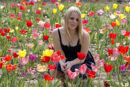 Blond girl in spring in a tulip field, Germany, Europe Stock Photo