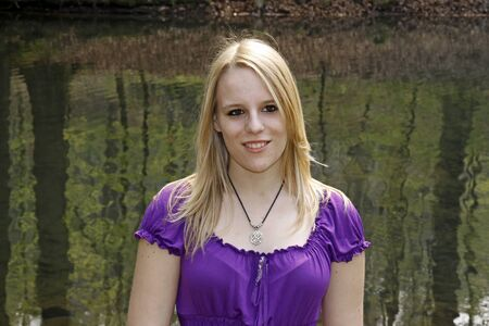 17 years: Young blonde 17 years old girl at a pond in spring, Casino park in Georgsmarienhuette, Lower Saxony, Germany
