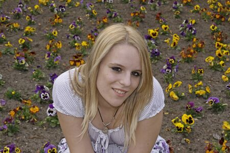 17 years: Young blond girl (17 years) in front of a flowerbed, Germany, Europe