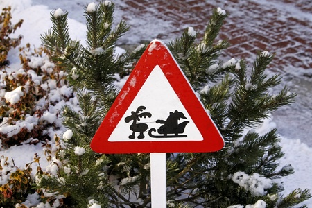Road sign with Santa Claus on sledges and reindeer in winter