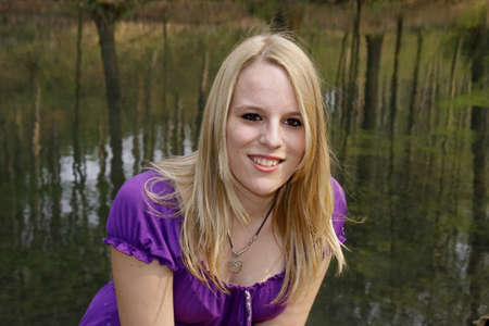 17 years: Young blond girl (17 years) at a pond in spring. Casino park in Georgsmarienhuette, Lower Saxony, Germany, Europe Stock Photo