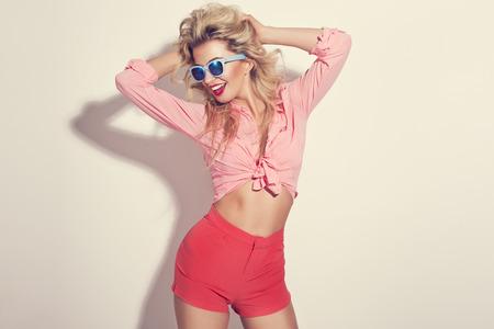 Fashion portret van blonde meisje met zonnebril draagt pastel stilering