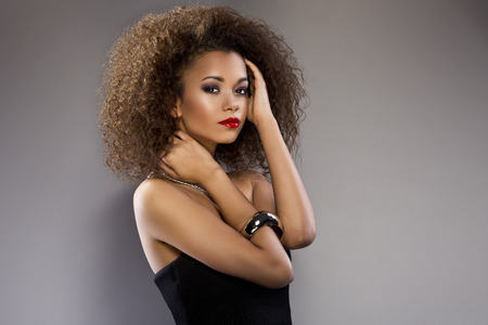 black fashion model: Beautiful young African American woman with an afro in a fresh dark short summer dress posing holding up one edge of the flared skirt with a provocative expression on a dark gray background Stock Photo