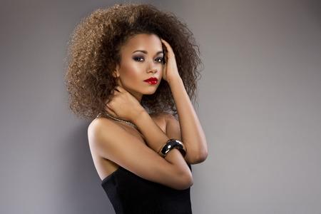 hair curly: Joven mujer afroamericana hermosa con un afro en un fresco vestido oscuro posando corto verano la celebración de un borde de la falda acampanada con una expresión provocativa sobre un fondo gris oscuro Foto de archivo