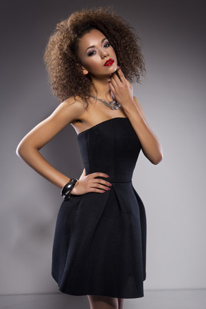 Beautiful young African American woman with an afro in a fresh dark short summer dress posing holding up one edge of the flared skirt with a provocative expression on a dark gray background Stock Photo