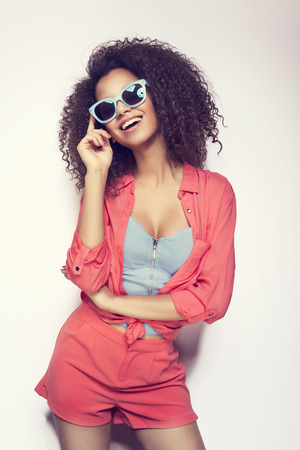 Laughing African young woman with an afro hairstyle wearing sunglasses and crayon stylization Stock Photo