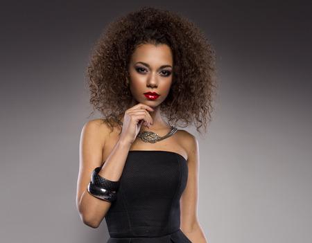 plan éloigné: Belle jeune femme afro-américaine avec un afro dans un endroit sombre courte robe d'été pose frais jusqu'à la tenue d'un bord de la jupe évasée avec une expression provocatrice sur un fond gris foncé Banque d'images