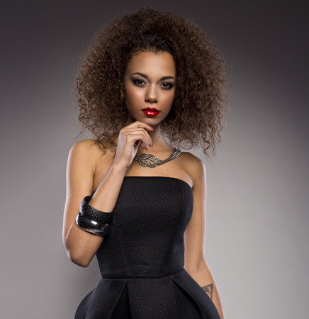 afro hair: Beautiful young African American woman with an afro in a fresh dark short summer dress posing holding up one edge of the flared skirt with a provocative expression on a dark gray background Stock Photo