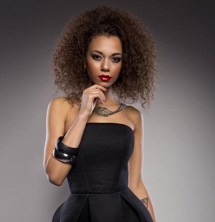 Schöne junge afroamerikanische Frau mit einem Afro in einem frischen dunklen kurzen Sommerkleid posiert hält eine Kante des ausgestelltem Rock mit einem provokativen Ausdruck auf einem dunkelgrauen Hintergrund Standard-Bild