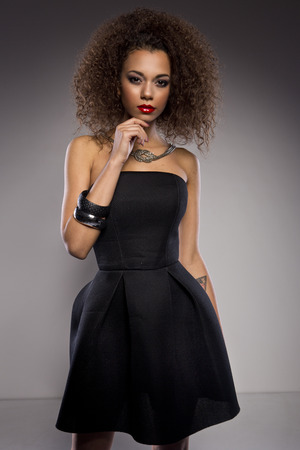 sexy image: Beautiful young African American woman with an afro in a fresh dark short summer dress posing holding up one edge of the flared skirt with a provocative expression on a dark gray background Stock Photo