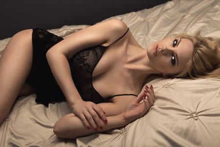 fille nue sexy: Sensuelle femme blonde posant en lingerie noire sur le lit. Banque d'images