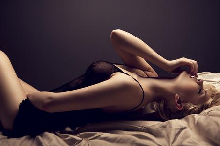 beaux seins: Sensuelle femme blonde posant en lingerie sexy noire Banque d'images