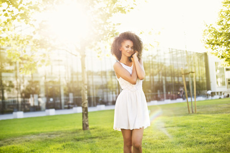 enlightenment: Enjoyment free happy african american woman with an afro enjoying sunset. Beautiful woman in white dress embracing the golden sunshine in the city