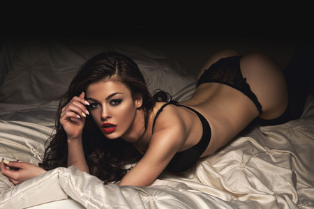 nude ass: Sexy beautiful brunette woman lying in bed in sensual black lingerie looking at camera.