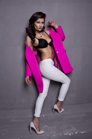 short sale: beautiful young brunette woman wearing pink jacket sensual black bra