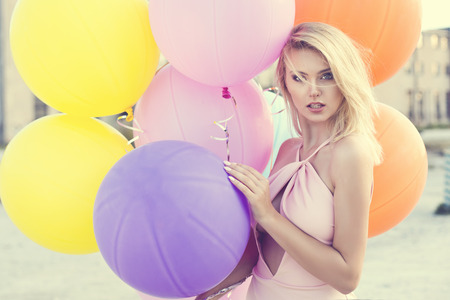 beautiful blonde happy woman with colorful pastel balloons in the city photo