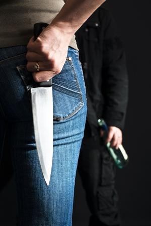 violencia intrafamiliar: Mujer con un cuchillo frente a su marido borracho.