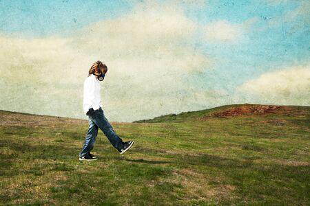 A boy wearing a gas mask walking on the meadow photo