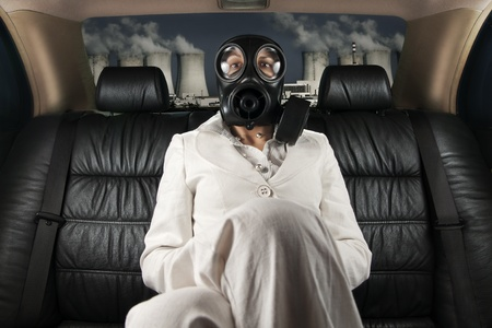 Lady in a gas mask on the back seat of limousine photo