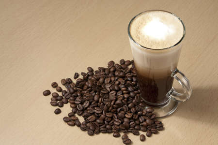latte macchiato: Coffee with froth and coffee beans below on the table  Horizontal Stock Photo