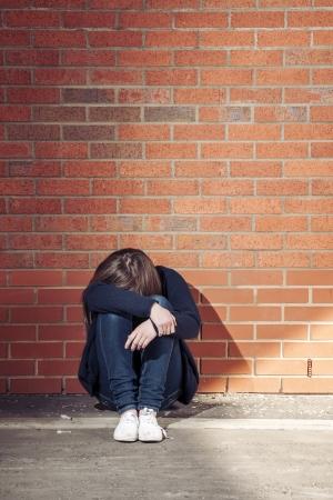 hoer: Addicted, verdrietig jonge vrouw tegen de bakstenen muur met een spuit naast. Verticaal.