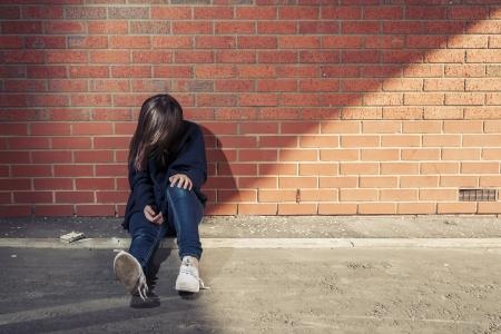 hoer: Addicted, verdrietig jonge vrouw tegen de bakstenen muur met spuit en sigaretten naast. Horizontaal.
