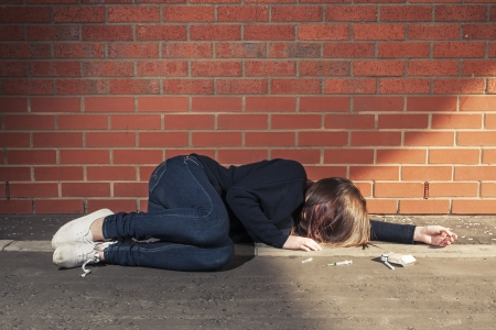 whore: Addicted, sad young woman lying against the brick wall with syringe and cigarettes beside.  Horizontal. Stock Photo