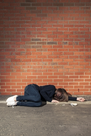 Addicted, sad young woman lying against the brick wall with syringe and cigarettes beside. Vertical. photo