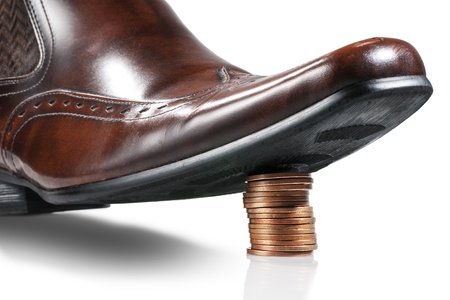 insolvency: Shiny businessman shoe step on the stack of coins  Isolated  Stock Photo