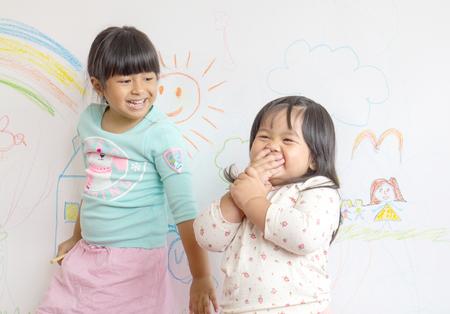 Due piccoli bambini sorridenti nel sorteggio sulla parete.