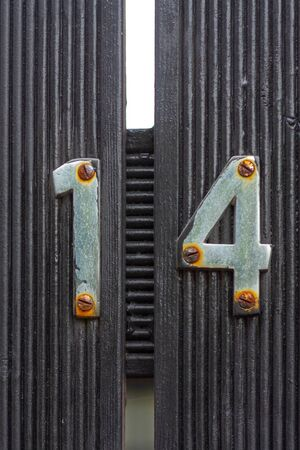 House number 14 on a black wooden gate