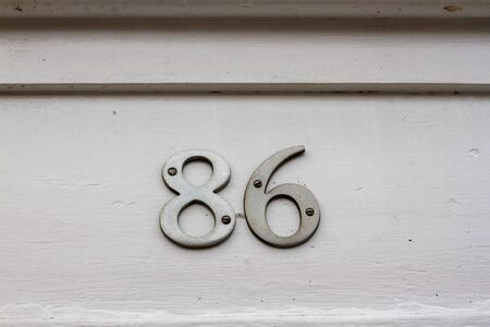 House number 86 on a white wall